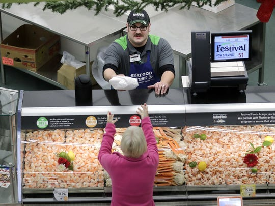 University Avenue Festival Foods meat and seafood manager Jonathan Doxtator serves a customer at the seafood case Friday.