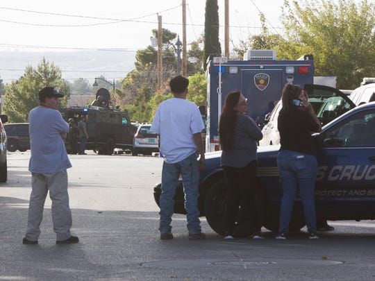 Las Cruces SWAT responding to a call on Texas Avenue, where two suspects barracked themselves in house after LCPD attempted to arrest them on felony warrents. Friday November 17, 2017.  Neighbors and family members of one of the suspects wait at the intersection of Texas and Almendra st, as SWAT calls on the suspects to come to surrender to police.