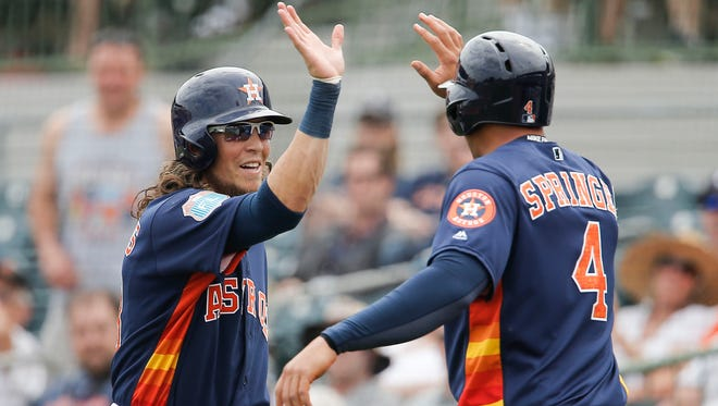 Houston Astros left fielder Colby Rasmus gets a high-five from George Springer after he hit a home run in spring training.