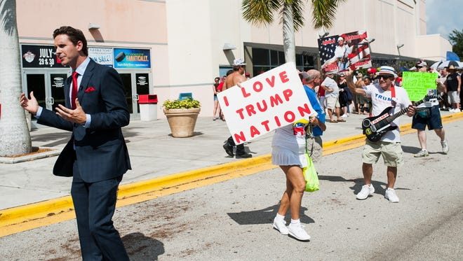 People wave signs at news crews outside of a Donald J. Trump rally at Germain Arena in Fort Myers, Fla., on Monday, Sept. 19, 2016.