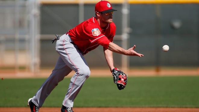 Cincinnati Reds shortstop Zack Cozart (2) flips the ball to second base during fielding drills at Cincinnati Reds spring training, Tuesday, Feb. 23, 2016, in Goodyear, Arizona.