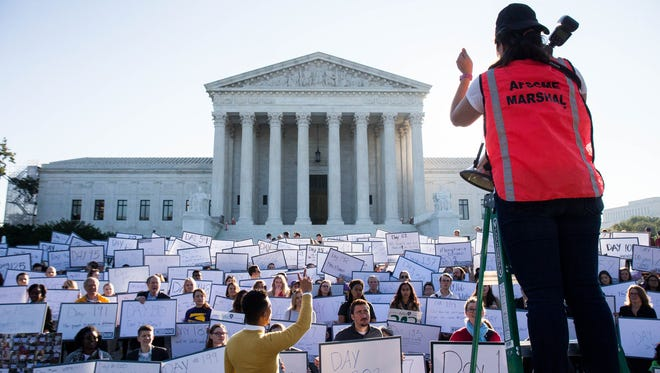 Lauren Santa Cruz, with The Hub Project, organizes protesters for a group photo during a demonstration urging the Senate to hold a confirmation vote for Supreme Court nominee Merrick Garland on Oct. 4, 2016.