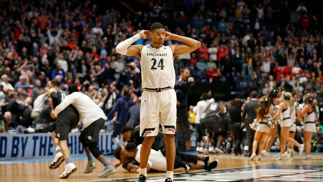 Cincinnati Bearcats forward Kyle Washington (24) walks off the court as the Nevada Wolf Pack celebrates on the floor after the final buzzer of the NCAA Tournament Second Round game between the Cincinnati Bearcats and the Nevada Wolf Pack at Bridgestone Arena in Nashville on Sunday, March 18, 2018. The 2-seeded Bearcats were eliminated from the tournament by the Wolf Pack with a 75-73 loss.