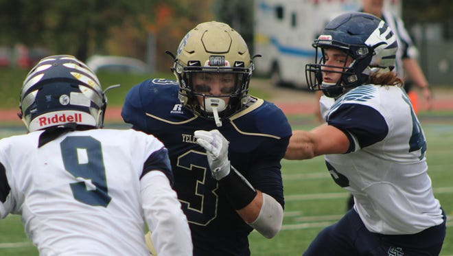 Country Day senior Nick Neibauer (3) splits Cranbrook defenders AJ Rodruguez (9) and Patrick Foley (45) during Saturday's pre-district battle. The host Yellowjackets won 35-7.