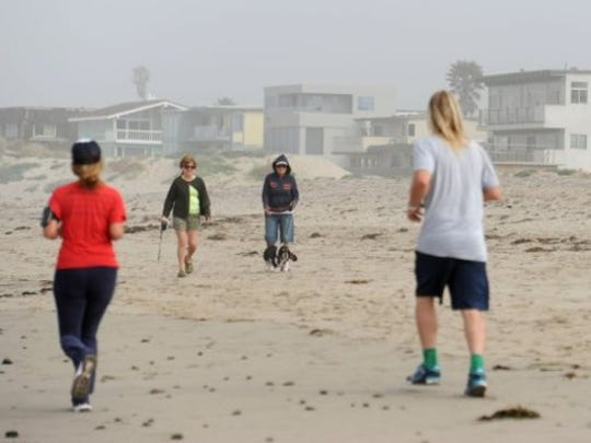 People stroll along Pierpont Beach in Ventura.