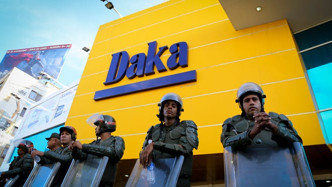 Soldiers stand guard outside one of the Daka stores that the Venezuelan government seized.
