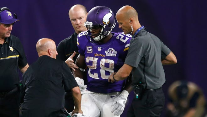 Adrian Peterson is helped off the field.