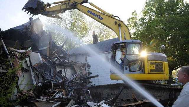 """DENNY SIMMONS / Courier & Press Kerry Wilhite uses his track excavator to tear down the house at 702 E. Iowa and 704 E. Iowa street as Roger Schmitt sprays water to keep the dust down Thursday morning. Nancy Bayer, a neighbor, watched the demolition from her home and said, """"I'm lovin' this."""""""