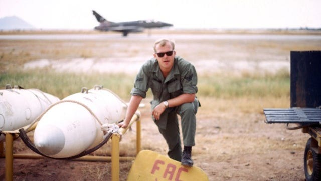 John Jetson served in Vietnam in 1969. Here he is with a  F-100 jet  in the background and the FAC U (Forward Air Control University) sign.  The forward air controller's expertise as an air strike controller  made him an intelligence source, munitions expert, communication specialist, and above all, the on-scene commander of the strike forces and the start of any subsequent combat search and rescue, if necessary.