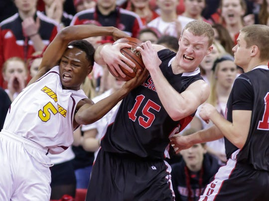 Milwaukee Young Coggs Prep's Tiwon Jones (5) and Washburn's Brant Schick battle for the ball during the first half of their Division 5 semifinals.