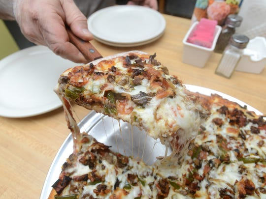 Joe Messina, owner of Joe's Family Restaurant in Roseville, puts a piece of the Steak Bomb Pizza on a plate. The restaurant just started serving pizza, and the Steak Bomb is a pizza version of the restaurant's popular Steak Bomb Sub.
