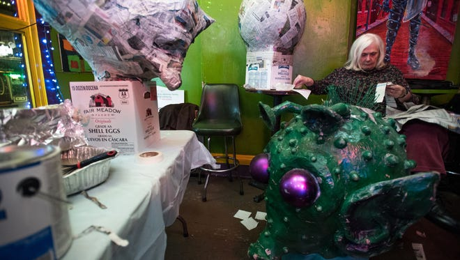 """Sonia Derge of Covington works on repairing a """"big head"""" at the Up Over Bar on Feb. 6 for the Covington Mardi Gras Grande Parade on Feb. 25."""