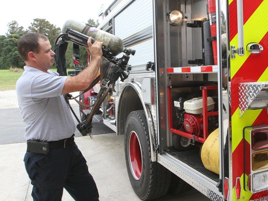 Capt. Doug Underwood, of the Bayshore Fire District, checks the equipment on one of their trucks last week.