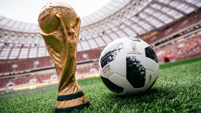 An adidas official match ball, named Telstar 18, sits next to the FIFA World Cup trophy in Luzhniki Stadium in Moscow.