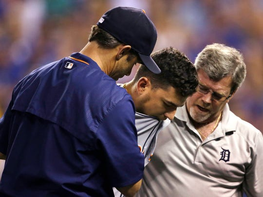 Detroit Tigers manager Brad Ausmus, left, and a team trainer, right, help Jose Iglesias off the field after an injury duirng the third inning of a baseball game against the Kansas City Royals at Kauffman Stadium in Kansas City, Mo., Thursday, Sept. 3, 2015. Iglesias injured his hand trying to bunt.