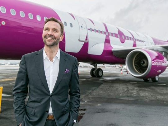 WOW CEO Skuli Mogensen stands in front of one of the airline's purple Airbus A321 aircraft.