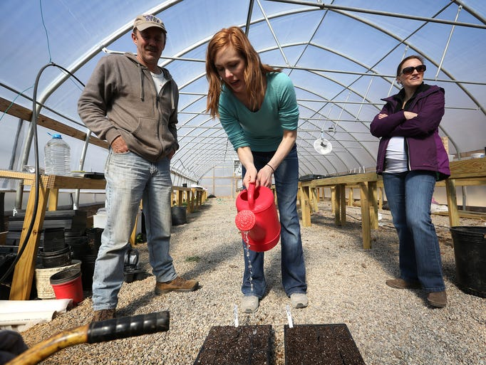 Jenna Sproul, center, waters seeds as Stephen Bartlett, left, supervises at a workshop geared towards amateur gardeners during a produce sale put on by Louisville Grows. Mar. 15, 2014.
