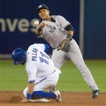 Toronto Blue Jays' Kevin Pillar is forced out at second as New York Yankees' Starlin Castro makes an errant throw to first trying to turn the double play on Josh Donaldson during the fifth inning of a baseball game Tuesday, April 12, 2016, in Toronto.