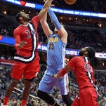 Washington Wizards guard John Wall (2) knocks the ball away from Denver Nuggets center Jusuf Nurkic (23) during the first half of an NBA basketball game Thursday, Jan. 28, 2016, in Washington. At right is Wizards center Nene. (AP Photo/Nick Wass)