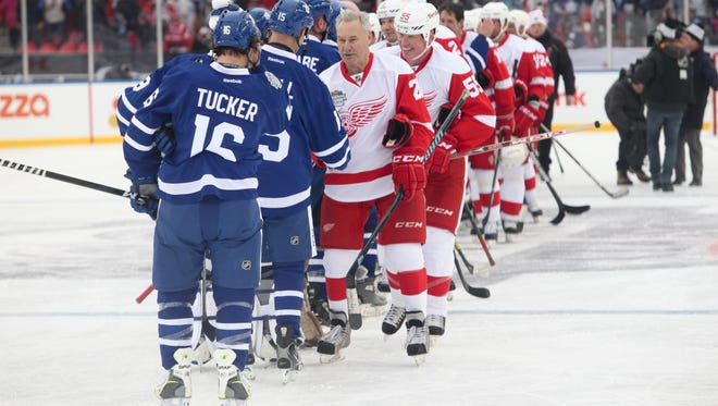 Former Red Wing and longtime Fox Sports Detroit hockey commentator Mickey Redmond leads the handshake line after the game.