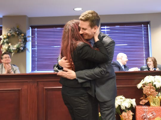 Newly elected committee member Marc Vojnich gets a hug from his wife, Erica Vojnich