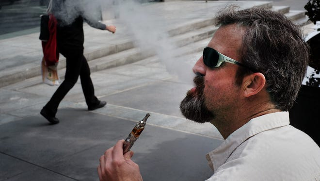 Paul Frohman smokes an electronic cigarette outside an office building in downtown Los Angeles on Wednesday, Jan. 28, 2015.