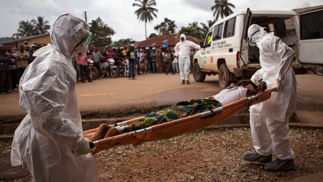 Hhealthcare workers load a man suspected of suffering from the Ebola virus onto an ambulance in Kenema, Sierra Leone on Sept. 24, 2014. Sierra Leone imposed a quarantine in a fishing district of the capital city, Freetown, after at least five new Ebola cases were confirmed there, an official said on Feb. 14, 2015.