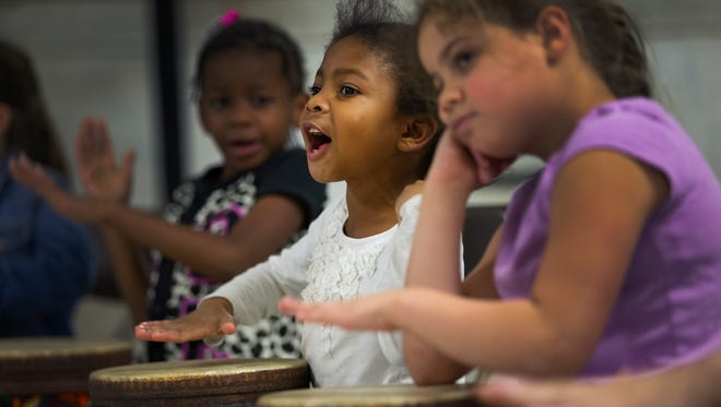 Kendra Davis, 6, plays a hand drum during a ROCMusic class led by Eastman students at Edgerton Recreation Center on Thursday.