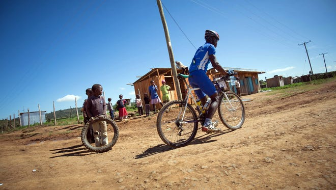 A handout picture taken on Nov. 23, 2015 shows children looking on as a rider in the Mt. Kenya Epik cycling challenge rides through a rural village in Laikipia County, 156 miles north of the Kenyan capital Nairobi.