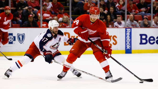 Detroit Red Wings center Gustav Nyquist (14) skates with the puck defended by Columbus Blue Jackets center Brandon Dubinsky (17) in overtime at Joe Louis Arena. Detroit won 2-1in a overtime shootout.