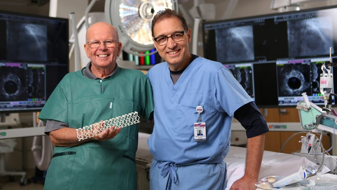Dr. David Rizik (right) and a team of HonorHealth doctors implanted the first commercial fully dissolvable stent in Doug Taylor (left) on Wednesday. Taylor, here holding an enlarged model of the dissolvable stent, is recovering well, doctors say.