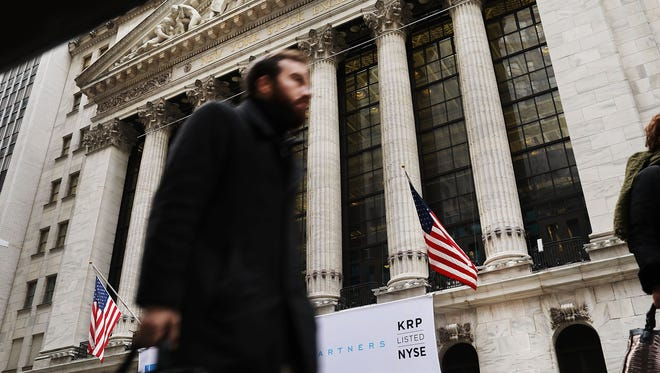 People walk by the New York Stock Exchange (NYSE) on Feb. 3, 2017 in New York City.