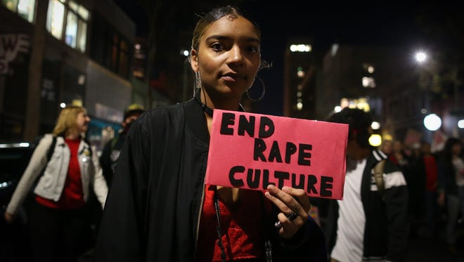 "A woman holds a sign reading ""End Rape Culture"" during a march for International Women's Day on March 8, 2017 in Oakland, Calif."
