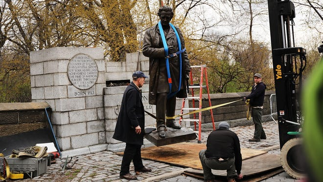A statue of J. Marion Sims is moved after being taken off its pedestal.