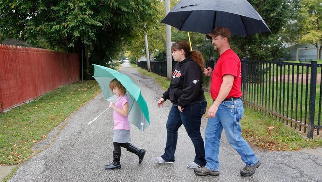 Rob and Toni Lear are joined by their six-year-old daughter, Cierra, on a walk through their north side neighborhood Wednesday, October 12, 2016, in Lafayette. Toni Lear said she walks through the neighborhood daily to keep an eye out for suspicious activity.