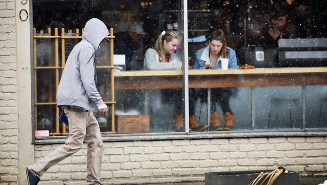 This is a weather photo. Two young girls keep warm inside of Ridgewood Coffee Company as a pedestrian walks past as light snow falls at the corner of E. Ridgewood Ave. and Oak Street in Ridgewood on 03/08/18.