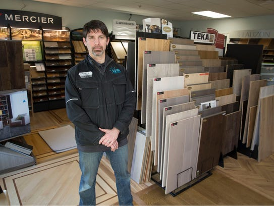 Adam Bissey, owner of Floors By The Shore, stands in