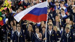 "FILE - In this Aug. 5, 2016, file photo, Sergei Tetiukhin carries the flag of Russia during the opening ceremony for the 2016 Summer Olympics in Rio de Janeiro, Brazil. The World Anti-Doping Agency declared Russia's scandal-ridden drug-fighting operation back in business Thursday, Sept. 20, 2018, a decision designed to bring a close to one of sports' most notorious doping scandals but one bitterly disputed by hundreds of athletes and described as ""treachery"" by the lawyer for the man who exposed the corruption. It also clears a major hurdle for Russia's track team to be declared compliant by that sport's international governing body (IAAF).(AP Photo/Matt Slocum, File)"