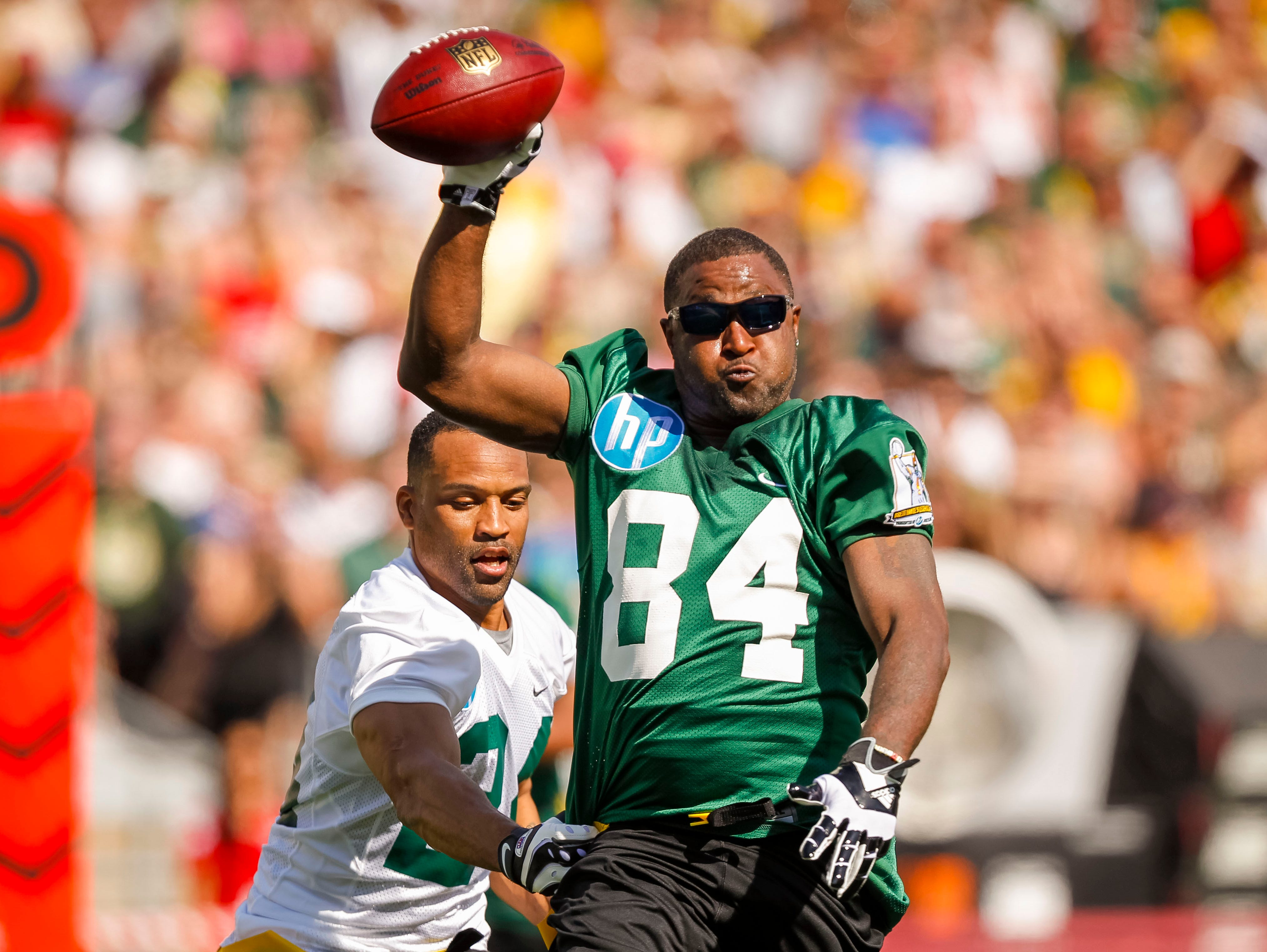 Former Green Bay Packers wide receiver Andre Rison (84) gets around former Arizona Cardinals safety Robert Griffith during a flag football game July 19, 2015, at Camp Randall Stadium in Madison, Wis.
