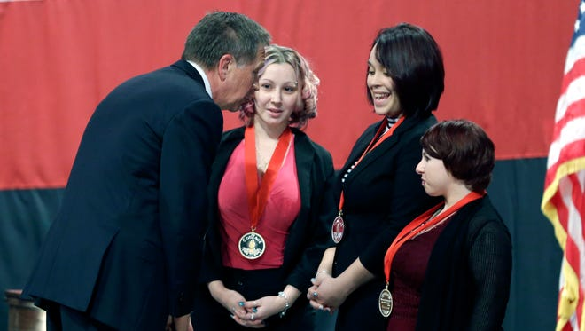 Ohio Gov. John Kasich, from left, talks with Amanda Berry, Gina DeJesus and Michelle Knight after they received the Governor's Courage Award, during Kasich's State of the State address in Feb. 24, 2014, in Medina, Ohio.