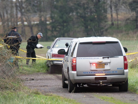 A medical examiner inspects a car allegedly used in