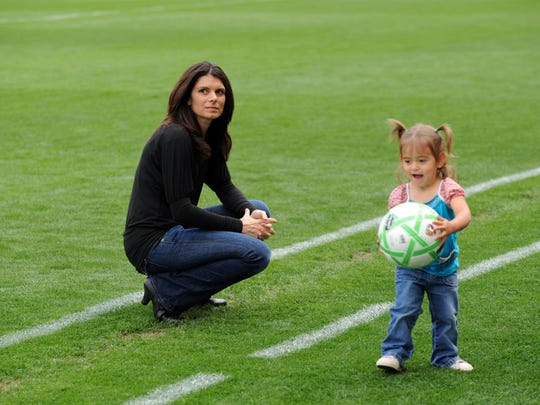 CARSON, CA - MARCH 29:  Mia Hamm looks on as her daughter plays with a ball prior to the match between the Washington Freedom and the Los Angeles Sol at The Home Depot Center on March 29, 2009 in Carson, California. The Sol defeated the Freedom 2-0. (Photo by Robert Laberge/Getty Images) (Via MerlinFTP Drop)