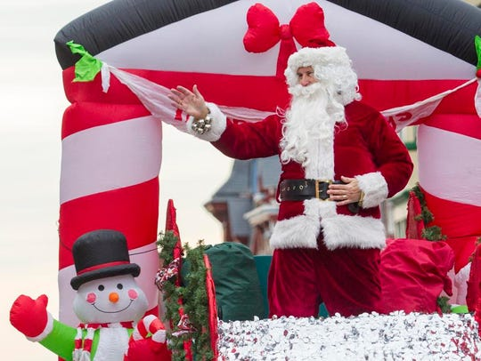 Santa Claus waves to spectators as he rides in the Wilmington Jaycees Christmas Parade in Wilmington in 2014.