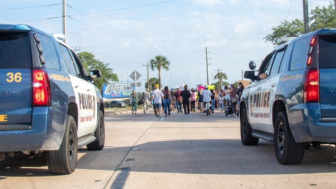 Officers from the St. Augustine Police Department stop traffic along U.S. 1 on Monday, June 1, as scores of people march to protest the death of George Floyd at the hands of police in Minneapolis, Minnesota.