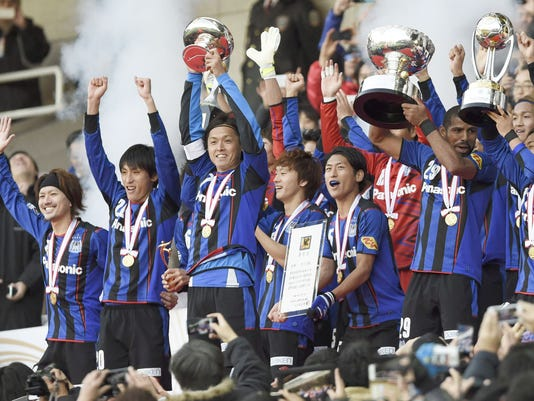 Gamba Osaka players celebrate with the trophies after they beat Montedio Yamagata 3-1 Saturday, Dec. 13, 2014, to win the Emperor's Cup and become the second team to complete a domestic treble, in Yokohama, near Tokyo. (AP Photo/Kyodo News) JAPAN OUT, CREDIT MANDATORY