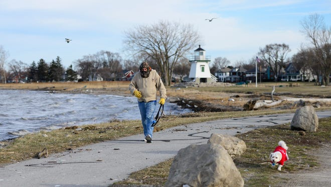 Jeff Auxter of Port Clinton walks his dog, Buddy, in 34-degree weather in Waterworks Park on Monday.