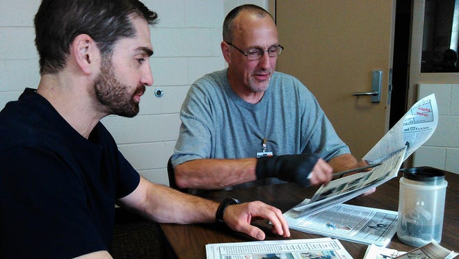 "Inmates Jon Schiefer, left, and Tom Schilling work on the next issue of ""The Oakdale Voice,"" a monthly newsletter officials say makes a positive contribution to the prison community in Coralville."