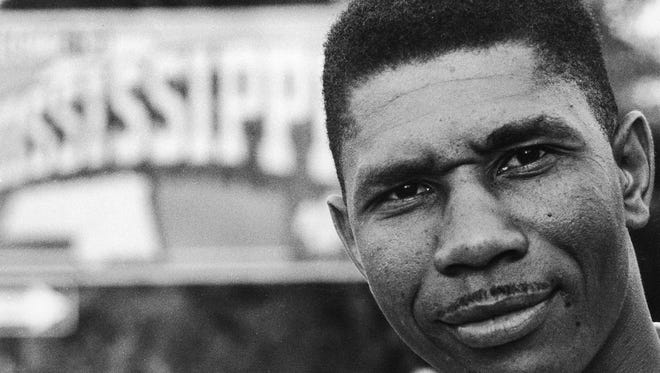 Medgar Evers, NAACP's first field secretary for the state of Mississippi stands nearby a sign of the state in this 1958 file photo.
