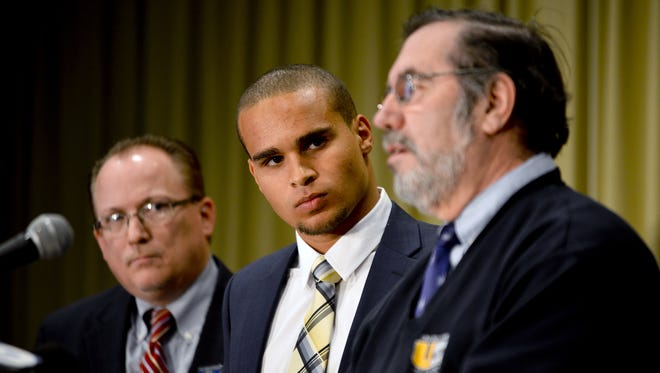 Former Northwestern quarterback Kain Colter (center) looks on as United Steelworkers (USW) president Leo W. Gerard speaks during a news conference for the College Athletes Players Association (CAPA) on Jan. 28 in Chicago. At left is United Steelworkers  (USW) national political director Tim Waters.