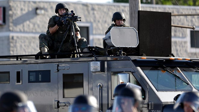 In this Aug. 9, 2014, file photo, a police tactical team moves in to disperse a group of protesters in Ferguson, Mo., that was sparked after Michael Brown, an unarmed black man was shot and killed by Darren Wilson, a white Ferguson police officer. College campuses also have received surplus military equipment from the Defense Department.